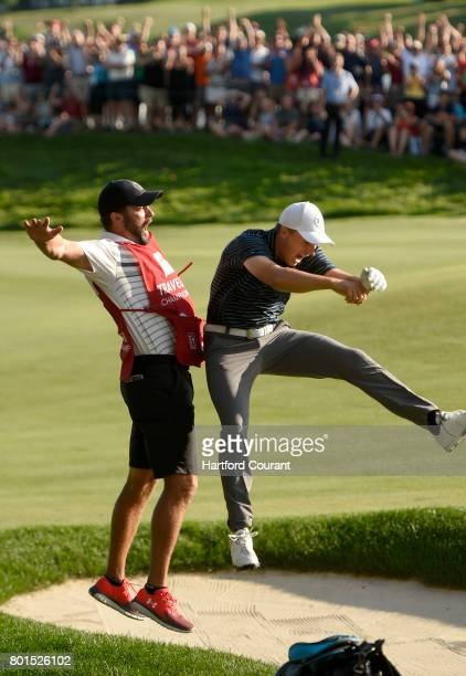 Jordan Spieth and his caddie Michael Greller celebrate after he holed his bunker shot on the 18th green for a birdie and win over Daniel Berger...