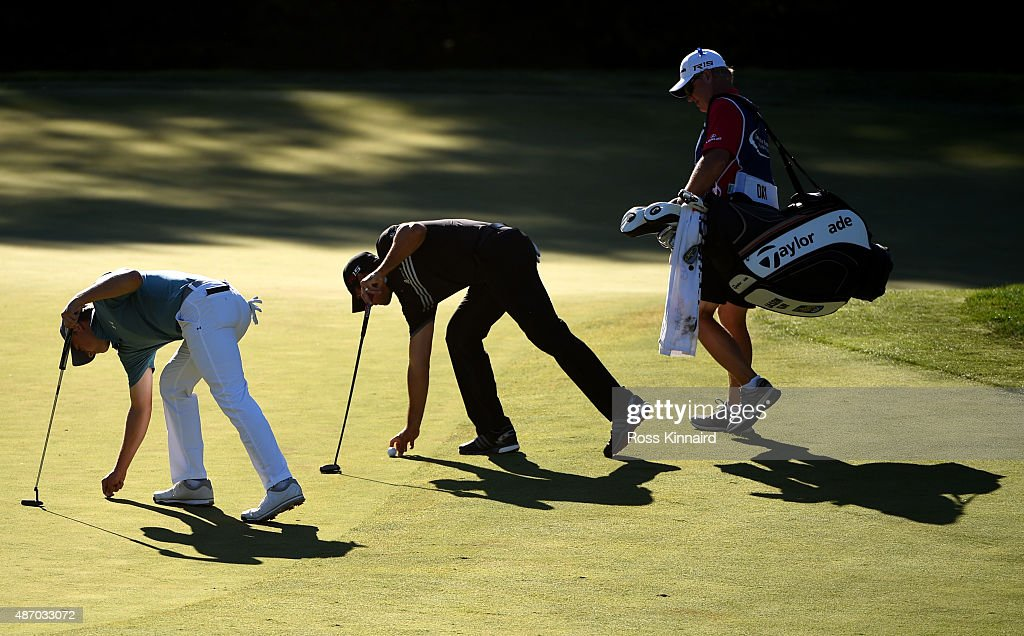 Jordan Spieth and Jason Day of Australia place their markers on the 12th green during round two of the Deutsche Bank Championship at TPC Boston on...