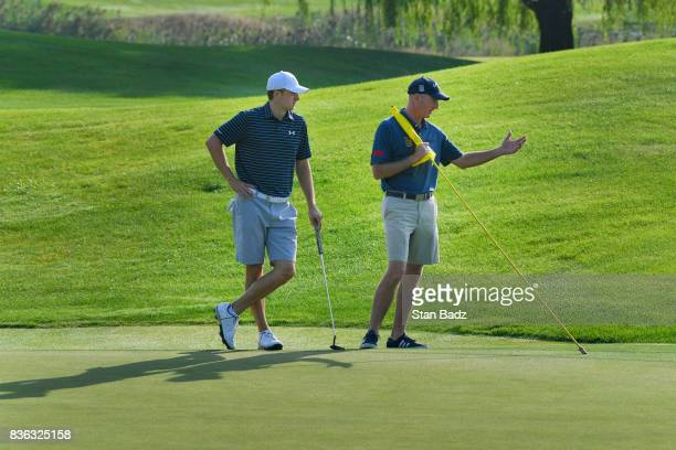 Jordan Spieth and United States Team captain's assistant Jim Furyk watch play on the third hole during course previews at Liberty National Golf Club...