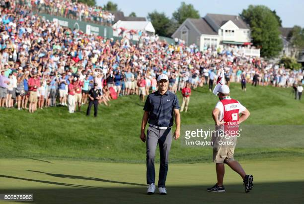 Jordan Spieth celebrates after holing his sand trap shot on the eighteenth the first play off hole to win the Travelers Championship Tournament at...