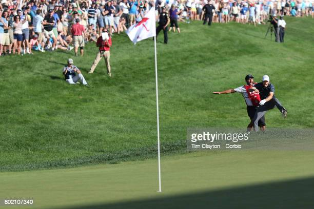 Jordan Spieth celebrates with his caddie Michael Greller after holing his sand trap shot on the eighteenth during the first play off hole of the...