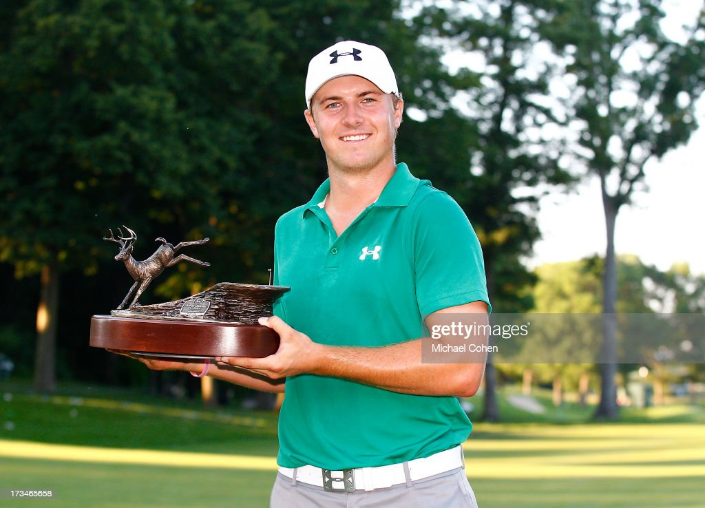 Jordan Spieth holds the trophy after winning a three way five hole sudden death playoff after the final round of the John Deere Classic held at TPC...
