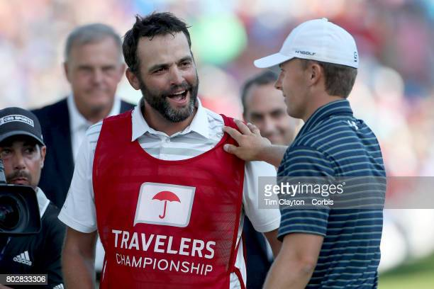 Jordan Spieth is congratulated by his caddie Michael Greller after winning the Travelers Championship Tournament at the TPC River Highlands Golf...
