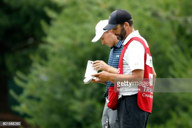 Jordan Spieth of the United States and caddie Michael Greller brush up on the 8th green during the final round of the Travelers Championship on June...