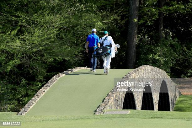 Jordan Spieth of the United States and caddie Michael Greller cross the Hogan Bridge during the final round of the 2017 Masters Tournament at Augusta...