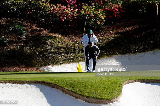Jordan Spieth of the United States and caddie Michael Greller line up a putt on the 12th green during the third round of the 2016 Masters Tournament...