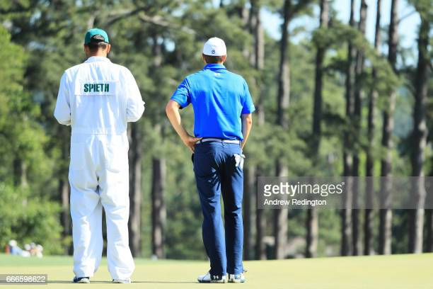 Jordan Spieth of the United States and caddie Michael Greller look on from the eighth hole during the final round of the 2017 Masters Tournament at...
