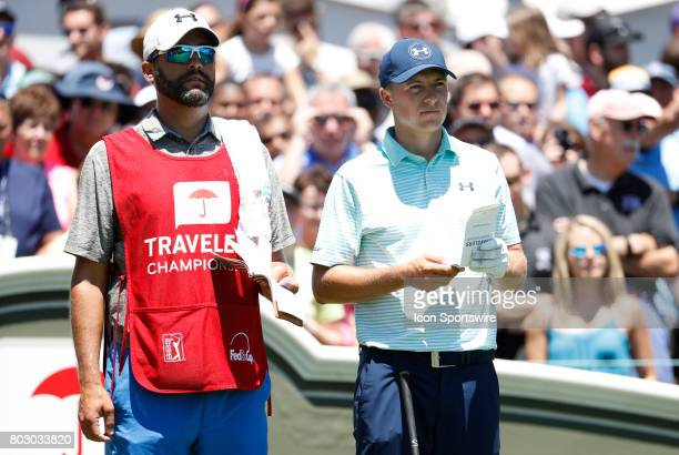 Jordan Spieth of the United States and caddie Michael Greller look down the first fairway during the third round of the Travelers Championship on...