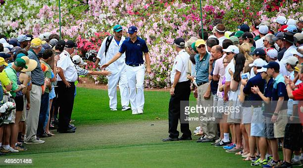Jordan Spieth of the United States and his caddie Michael Greller walk to the sixth green during the final round of the 2015 Masters Tournament at...
