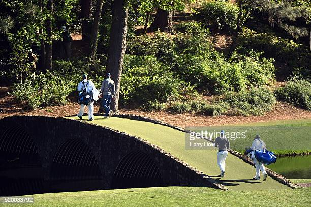 Jordan Spieth of the United States caddie Michael Greller Rory McIlroy of Northern Ireland and caddie JP Fitzgerald walk across the Hogan bridge to...