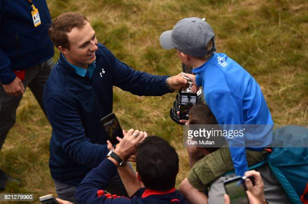 Jordan Spieth of the United States celebrates victory with a young fan as he walks with the Claret Jug around the 18th green during the final round...