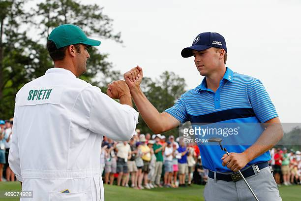 Jordan Spieth of the United States celebrates with his caddie Michael Greller on the 18th green after an eighthunder par 64 during the first round of...