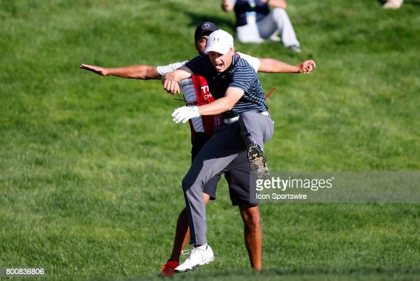 Jordan Spieth of the United States chest bumps caddie Michael Grellar after knocking it in from the bunker to win the Travelers Championship on June...