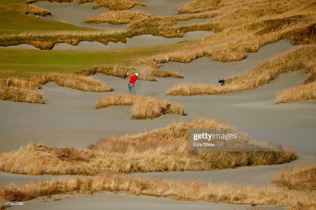 Jordan Spieth of the United States hits a shot from a bunker on the 18th hole during the third round of the 115th U.S. Open Championship at Chambers Bay on June 20, 2015 in University Place, Washington.