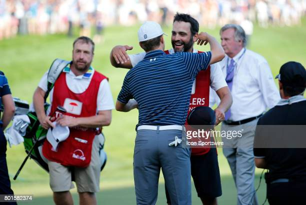 Jordan Spieth of the United States hugs his caddie Michael Greller after winning the final round of the Travelers Championship on June 25 at TPC...