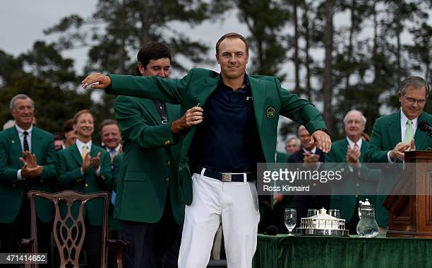 Jordan Spieth of the United States is presented with his Green Jacket by Bubba Watson of the United States after the final round of the 2015 Masters...