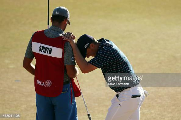 Jordan Spieth of the United States leans on his caddie Michael Greller after a birdie on the 18th green during the final round of the 115th US Open...