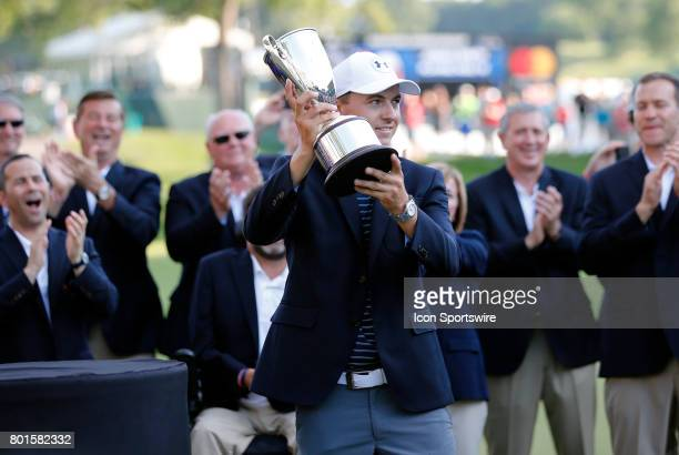 Jordan Spieth of the United States lifts the trophy during the final round of the Travelers Championship on June 25 at TPC River Highlands in...