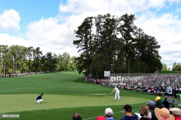 Jordan Spieth of the United States lines up a putt on the second green with the help of caddie Michael Greller during the first round of the 2017...