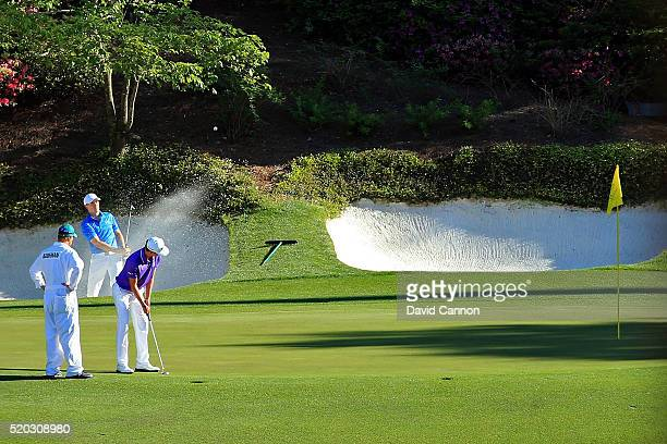 Jordan Spieth of the United States plays a shot from a bunker on the 12th hole as Smylie Kaufman of the United States and caddie Aaron Alpern look on...