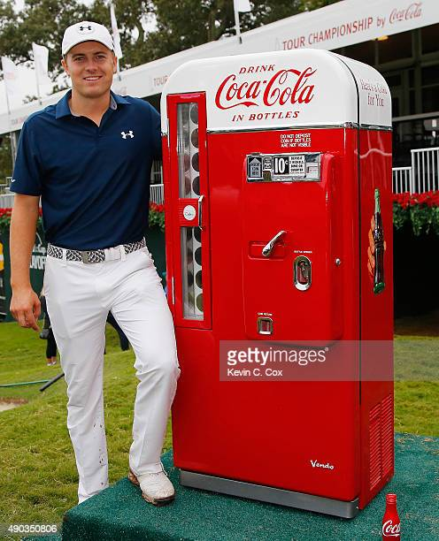 Jordan Spieth of the United States poses on the 18th green with a vintage CocaCola machine after winning both the TOUR Championship By CocaCola and...