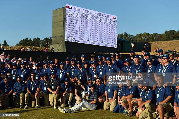 Jordan Spieth of the United States poses with the trophy amid the grounds crew after winning the 115th US Open Championship at Chambers Bay on June...