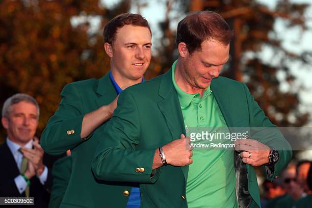 Jordan Spieth of the United States presents Danny Willett of England with the green jacket after Willet won the final round of the 2016 Masters...