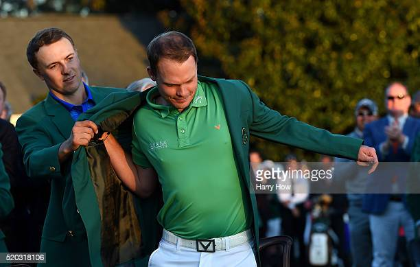 Jordan Spieth of the United States presents Danny Willett of England with the green jacket after Willett won the final round of the 2016 Masters...