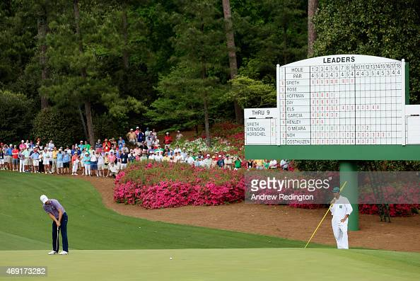 Jordan Spieth of the United States putts on the tenth hole as his caddie Michael Greller looks on during the second round of the 2015 Masters...