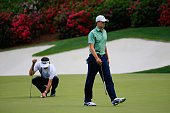 Jordan Spieth of the United States reacts to a missed putt on the 13th green as Bubba Watson lines up a putt during the final round of the 2014...