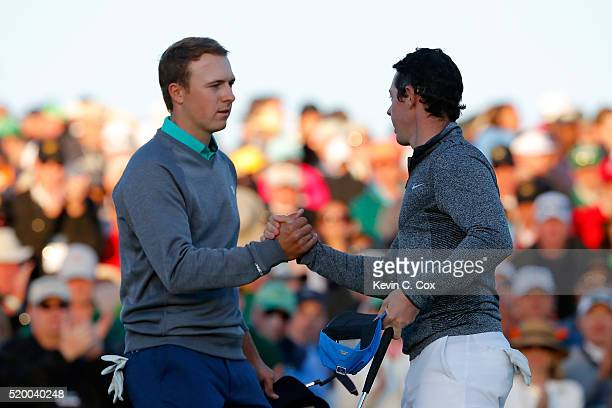 Jordan Spieth of the United States shakes hands with Rory McIlroy of Northern Ireland on the 18th green during the third round of the 2016 Masters...