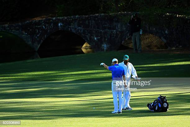 Jordan Spieth of the United States takes his first drop on the 12th hole as caddie Michael Greller looks on during the final round of the 2016...