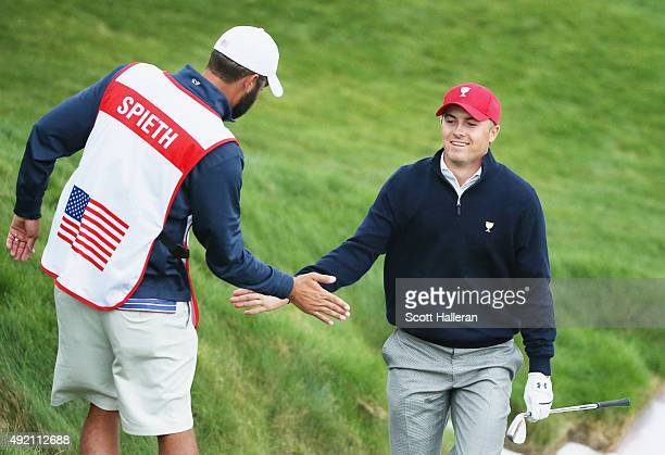 Jordan Spieth of the United States Team celebrates with his caddie Michael Greller after holing a bunker shot on the 12th hole during the Saturday...