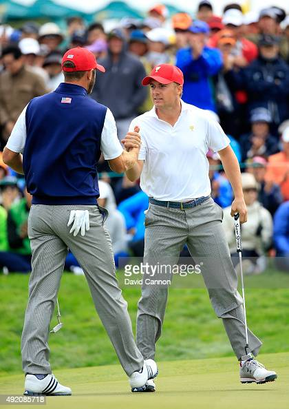Jordan Spieth of the United States team is congratulated by his partner Dustin Johnson after he had holed a match winning par putt on the 18th hole...
