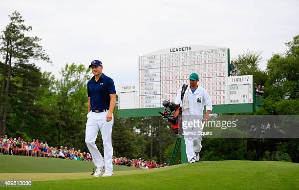 Jordan Spieth of the United States walks across the 18th green with his caddie Michael Greller during the final round of the 2015 Masters Tournament...