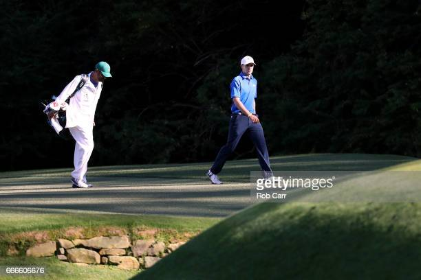 Jordan Spieth of the United States walks with caddie Michael Greller on the 13th hole during the final round of the 2017 Masters Tournament at...
