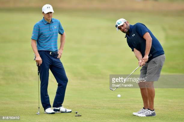 Jordan Spieth of the United States watches his caddie Michael Greller chip during a practice round prior to the 146th Open Championship at Royal...