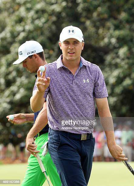 Jordan Spieth of the United States waves to the gallery after saving par on the first hole as Billy Horschel walks past during the second round of...