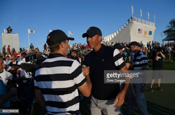 Jordan Spieth of the US Team and Matt Kuchar of the US Team shake hands after their match during the first round of the Presidents Cup at Liberty...