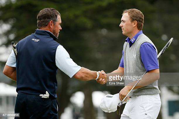 Jordan Spieth shakes hands with Lee Westwood of England after being eliminated following his loss in round three of the World Golf Championships...