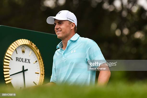 Jordan Spieth smiles before teeing off on the 18th hole tee box in front of the Rolex clock during the first round of The Barclays at Bethpage State...