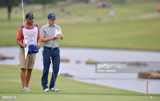 Jordan Spieth studies a putt with caddie Michael Greller on on the 18th green during Round Two of the ATT Byron Nelson at the TPC Four Seasons Resort...