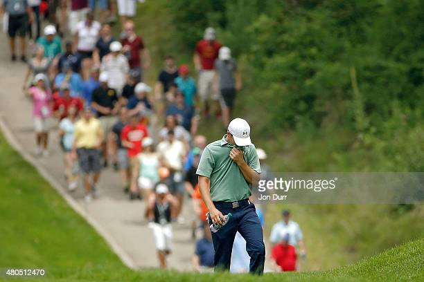 Jordan Spieth walks up the first fairway to his ball on the outside of the cart path during the final round of the John Deere Classic held at TPC...