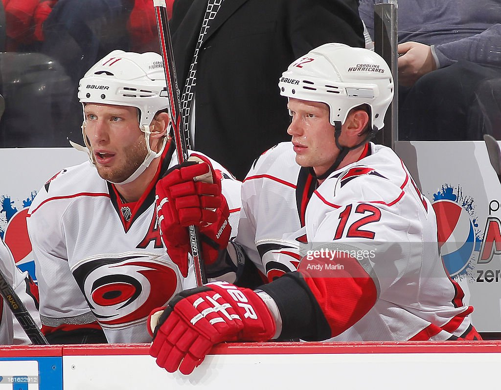Jordan Staal #11 and Eric Staal #12 of the Carolina Hurricanes look on from the bench against the New Jersey Devils during the game at the Prudential Center on February 12, 2013 in Newark, New Jersey.