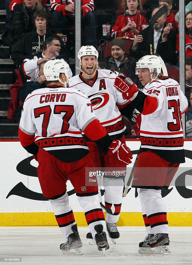 Jordan Staal #11 and Joe Corvo # 77 of the Carolina Hurricanes congratulate teammate Jussi Jokinen #36 after Jokinen scored in the second period against the New Jersey Devils at the Prudential Center on February 12, 2013 in Newark, New Jersey.