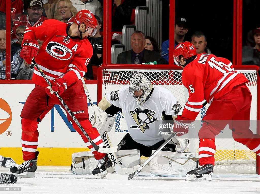 Jordan Staal #11 and Tuomo Ruutu #15 of the Carolina Hurricanes search for a puck at the pads of Marc-Andre Fleury #29 of the Pittsburgh Penguins during their NHL game at PNC Arena on October 28, 2013 in Raleigh, North Carolina.
