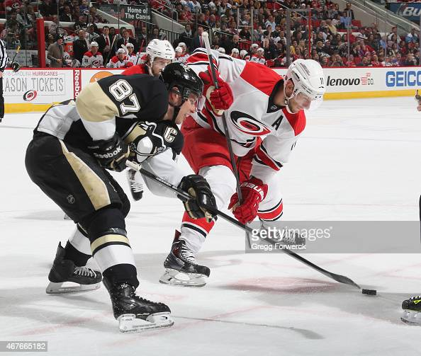 Jordan Staal of the Carolina Hurricanes and Sidney Crosby of the Pittsburgh Penguins battle for the puck during their NHL game at PNC Arena on March...