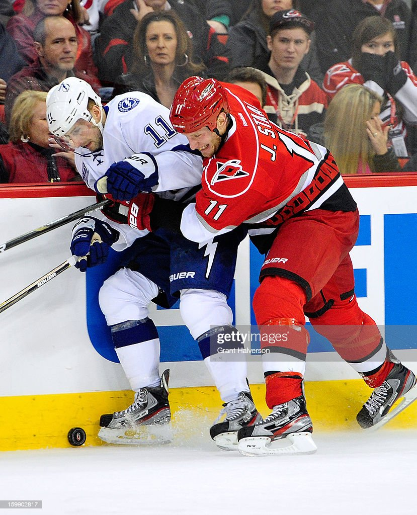 Jordan Staal #11 of the Carolina Hurricanes battles for the puck with Tom Pyatt #11 of the Tampa Bay Lightning during play at PNC Arena on January 22, 2013 in Raleigh, North Carolina.
