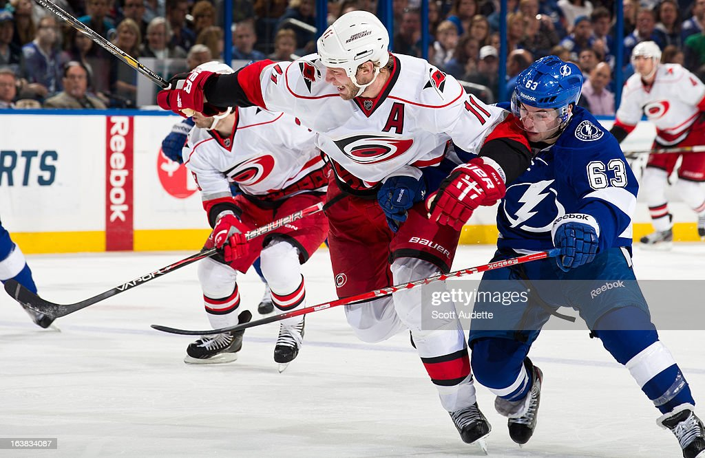 <a gi-track='captionPersonalityLinkClicked' href=/galleries/search?phrase=Jordan+Staal&family=editorial&specificpeople=533044 ng-click='$event.stopPropagation()'>Jordan Staal</a> #11 of the Carolina Hurricanes fights for position against <a gi-track='captionPersonalityLinkClicked' href=/galleries/search?phrase=Tyler+Johnson+-+Ice+Hockey+Player&family=editorial&specificpeople=14574766 ng-click='$event.stopPropagation()'>Tyler Johnson</a> #63 of the Tampa Bay Lightning during the second period of the game at the Tampa Bay Times Forum on March 16, 2013 in Tampa, Florida.