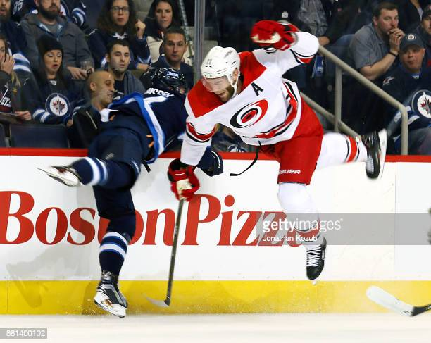 Jordan Staal of the Carolina Hurricanes gets airborne after colliding along the boards with Josh Morrissey of the Winnipeg Jets during first period...